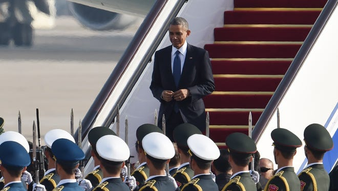 President Barack Obama walks down the stairs after disembarking from his plane at Beijing's international airport on November 10, 2014 as he arrives to take part in the Asia Pacific Economic Cooperation (APEC) Summit.