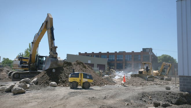 Construction Friday, June 17, 2016. includes new parking lots on property behind three buildings that are part of the expansion at Village Gate on North Goodman Street in Rochester.