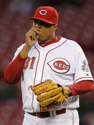 Cincinnati Reds starting pitcher Alfredo Simon (31) warms his hand between pitches in the top of the third inning of the MLB game between the Cincinnati Reds and the Pittsburgh Pirates at Great American Ball Park on Friday, April 8, 2016. After three innings the Reds led 3-1.