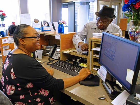 Bank teller Kendra Brown waits on customer Robert Crain, who has been a customer of Del.One Federal Credit Union since the mid 1960's.