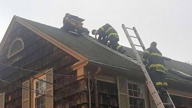 Before handing him off to Firefighter Joseph Infantini on the lower ladder, Firefighter Edgar Echavarria carries an 8-year-old boy down the roof where the boy was stuck. Capt. Christopher Beady, top, initially secured the child on the slippery roof in this May 2016 rescue.