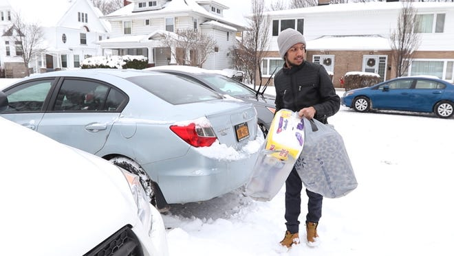 Bijaya Khadka of Rochester gets a blanket and toilet paper out of his car to deliver to a family at the same apartment complex he lives in.