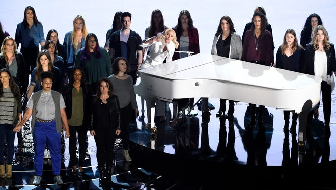 """Lady Gaga, center, performs """"Til It Happens To You,"""" nominated for best original song from """"The Hunting Ground,"""" on stage with survivors of abuse at the Oscars on Feb. 28, 2016 at the Dolby Theatre in Los Angeles."""