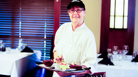 Sue Barras holds a tray of her desserts at Charley G's. She recently resumed her role as the restaurant's pastry chef after a few years away.