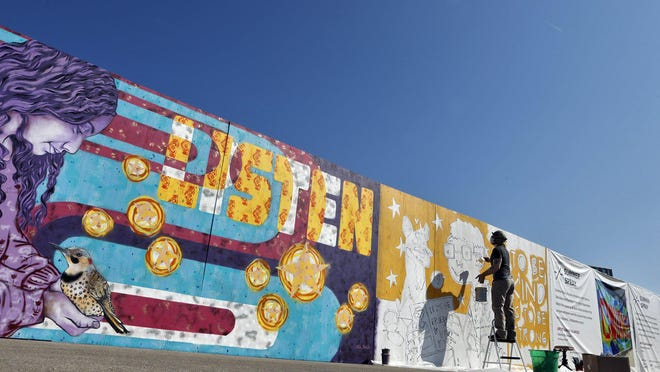Artist Thom Glick works on his portion of the Summer Spray mural along Goodale Boulevard last weekend. The section on the left was completed by Eric Rausch and his wife, Jen Kiko.