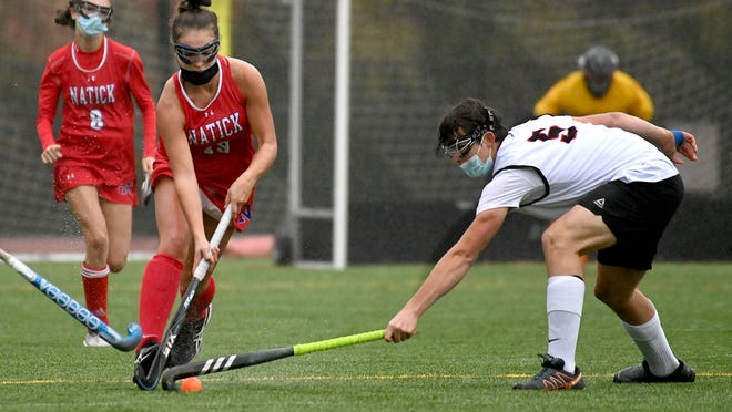 Natick's Emma Peck looks to pass as Wellesley's Edward Webb (right) gets a stick in during the first half Wednesday at Wellesley High School.