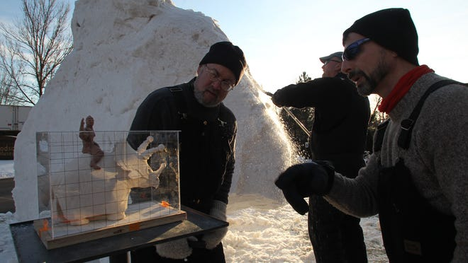 Team USA snow sculptors, from left, Michael Sponholtz, Tom Queoff and Mike Martino work on turning the model of a boy riding a ticeratops, left, into a snow sculpture in 2012 at the Woodson Art Museum in Wausau. The team's talents will be on display during the Mishicot Winterfest on Feb. 21.
