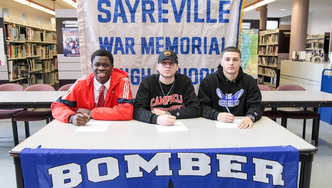 Sayreville football players sign their National Letters of Intent on Wednesday. (From left) Jahsim Floyd, Saint Francis University, Jayson DeMIld, Campbell University, and Andrew Wille, Southern Connecticut University.