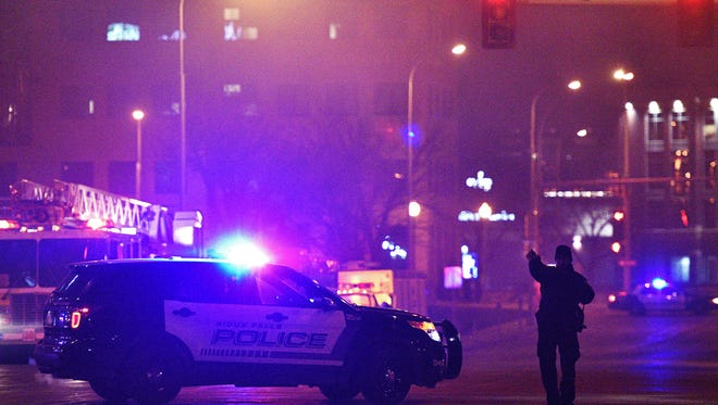 A police officer with the Sioux Falls Police Department blocks the intersection of 11th Street and Second Avenue during a fire in 2016.