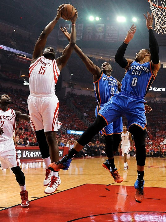 Houston Rockets forward Montrezl Harrell (5) grabs a rebound over Oklahoma City Thunder guards Victor Oladipo (5) and Russell Westbrook during the first half in Game 2 of an NBA basketball first-round playoff series, Wednesday, April 19, 2017, in Houston. (AP Photo/Eric Christian Smith)