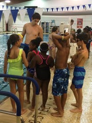 Farmington Family YMCA swim instructor Louis Senia-Grant gives safety instructions to students participating in the World's Largest Swim Lesson on Thursday.