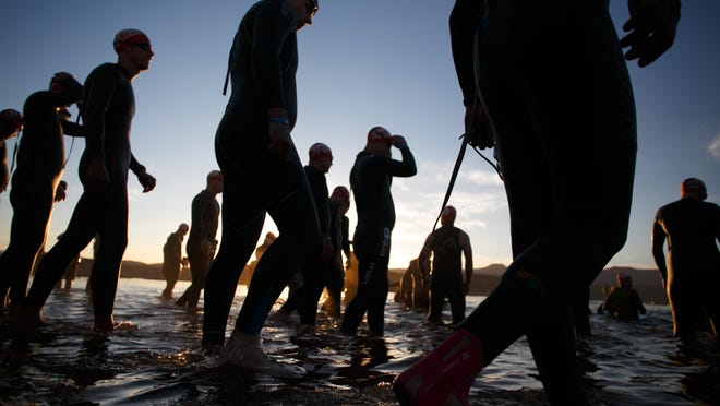 Ironman competitors enter the water at Sand Hollow Reservoir prior to the start of the 2015 Ironman St. George 70.3 mile race Saturday, May 2, 2015.