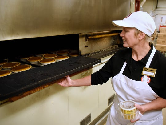 Bakery manager Donna Ramstad opens the oven as pumpkin