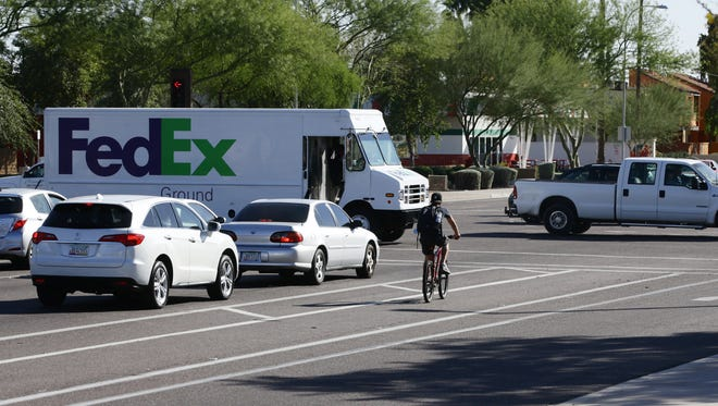 A bicyclist waits in the bike lane for the light to change at McClintock Drive and Broadway Road on Nov. 17, 2016, in Tempe.