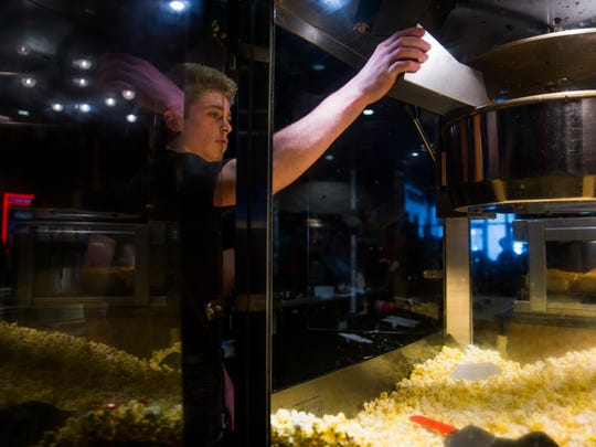 Trevor Kinnee, 16, refills the popcorn machine at Paragon Pavilion theater in December 2016 in North Naples.