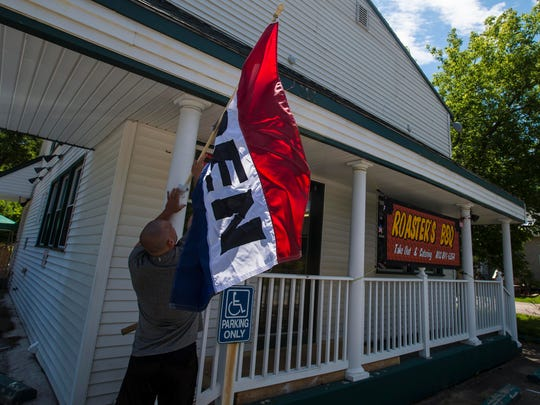 "Travis Leroux puts out an OPEN flag at Roaster's BBQ in Milton on Tuesday, July 12, 2016. Travis is the brother of the restaurant's owner, self-described ""Pig-roaster extraordinaire"" Trevor Leroux."