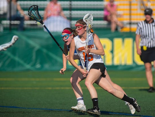 Middlebury's Andi Boe brings the ball down the field in front of Mt. Anthony's Isabelle Small during the Division I girls lacrosse high school state championship on Monday, June 12, 2017.