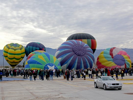 Hot-air balloons begin inflating during a previous