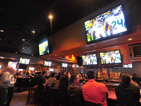 Football fans watch a game at Walk-On's Bistreaux & Bar in Lafayette.
