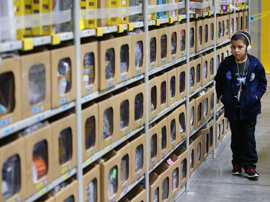 Ben Bicknese, age 8 from Tucson, walks down an aisle filled with merchandise at the Amazon Fulfillment Center PHX6 during a special tour on Jan. 10, 2017, in Phoenix, Ariz. The trip marked one of the first trips Bicknese has taken out of his home, following several rounds of chemotherapy he completed in October of 2016.