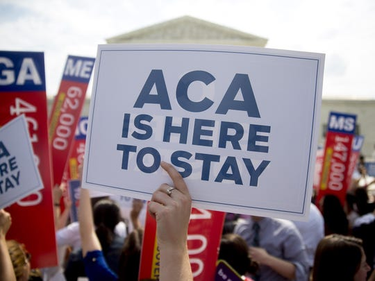 """A demonstrator in support of U.S. President Barack Obama's health-care law, the Affordable Care Act (ACA), holds up a """"ACA is Here to Stay"""" sign after the U.S. Supreme Court ruled 6-3 to save Obamacare tax subsidies outside the Supreme Court in Washington, D.C., U.S., on Thursday, June 25, 2015."""