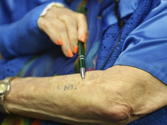 Eva Kor points to the tattoo that was placed on her arm upon her internment at Auschwitz.