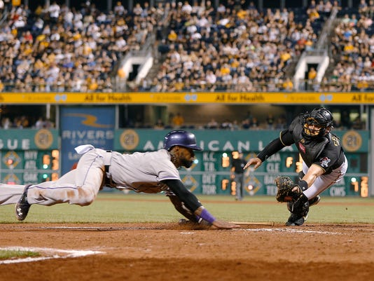 Colorado Rockies' Jose Reyes, left, dives for home plate before he is tagged out by Pittsburgh Pirates catcher Francisco Cervelli during the eighth inning of a baseball game, Friday, Aug. 28, 2015, in Pittsburgh. The Pirates won 5-3. (AP Photo/Keith Srakocic)