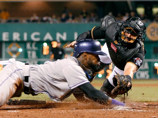 Colorado Rockies' Jose Reyes, left, is tagged out by Pittsburgh Pirates catcher Francisco Cervelli as he tries to score from third on a fly-out by Nolan Arenado during the eighth inning of a baseball game, Friday, Aug. 28, 2015, in Pittsburgh. The Pirates won 5-3. (AP Photo/Keith Srakocic)