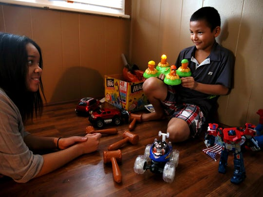 Angel Higginbottom, 15, left, daughter of Enquirer photojournalist Cara Owsley, talks with Josue Antonio Oviedo Sanchez, 9, in his home in Hamilton.