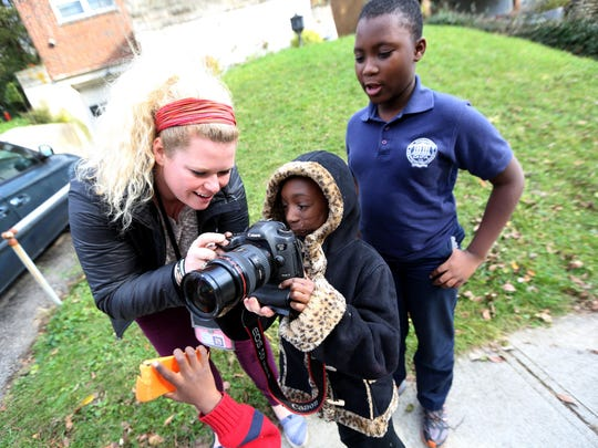 Enquirer photojournalist Meg Vogel shows Zainabou Drame, 7, and her brother Moustapha Drame, 10, how to use her camera outside their home.