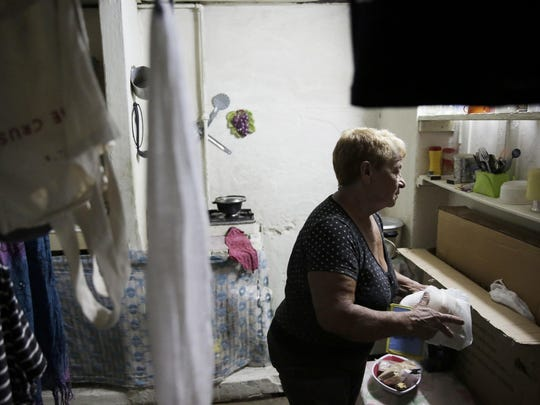 Alba Lara, 71, prepares dinner for herself in her Havana, Cuba, home on Tuesday, Nov. 29, 2016.