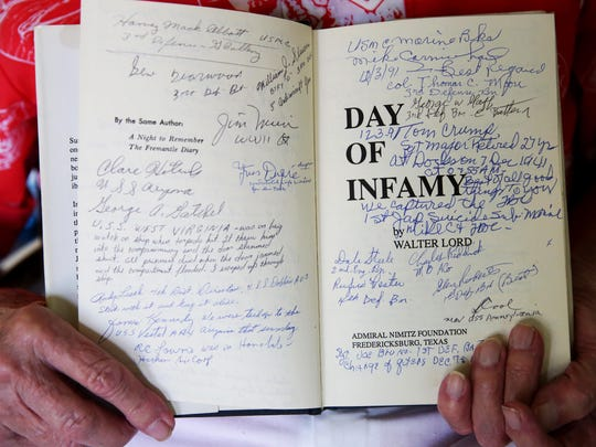 Smith holds a book signed by other survivors of the Pearl Harbor attack.