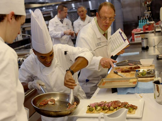 Chef Shawn Loving rushes to plate his final dish during day four of the American Culinary Federation's 2017 Certified Master Chef exam at Schoolcraft College in Livonia.