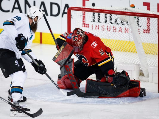 San Jose Sharks' Joe Thornton, left, has his shot blocked by Calgary Flames goalie Mike Smith during first-period NHL hockey game action in Calgary, Thursday, Dec. 14, 2017. (Jeff McIntosh/The Canadian Press via AP)