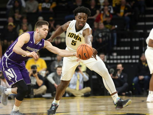 Northwestern's Bryant McIntosh and Iowa's Tyler Cook fight for the ball in an NCAA college basketball game in Iowa City, Iowa, Sunday, Feb. 25, 2018. (James Capen/Iowa City Press-Citizen via AP)