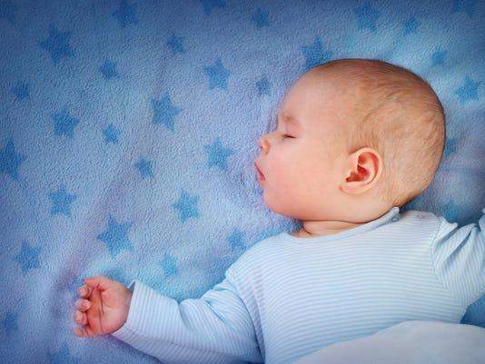 three month old baby sleeping on blue blanket