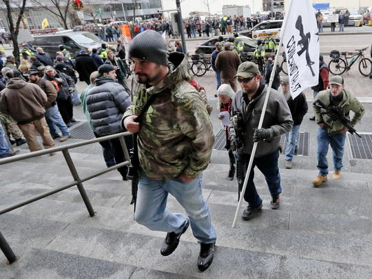 Protestors carrying rifles walk up the steps for a rally at the City County building on Monday, Jan. 7, 2019, in Pittsburgh. The protesters, many openly carrying guns, gathered in downtown Pittsburgh to rally against the city council's proposed restrictions and banning of semi-automatic rifles, certain ammunition and firearms accessories within city limits. (AP Photo/Keith Srakocic)
