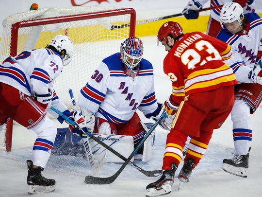 New York Rangers goalie Henrik Lundqvist (30) braces for a shot from Calgary Flames' Sean Monahan (23) during third-period NHL hockey game action in Calgary, Alberta, Thursday, Jan. 2, 2020. (Jeff-McIntosh/The Canadian Press via AP)