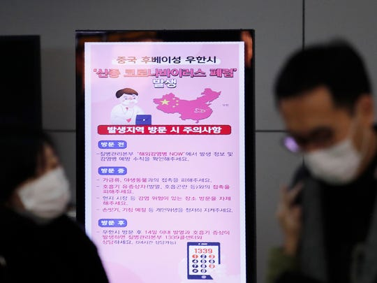 A poster warning about coronavirus is seen as passengers wear masks in a departure lobby at Incheon International Airport in Incheon, South Korea.
