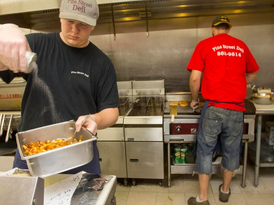Taylor Courville, a manager at the Pine Street Deli in Burlington, Vt., salts a large order of french fries during the lunchtime rush as Nick Sobolew, right works the grill, Tuesday, August 26, 2014.