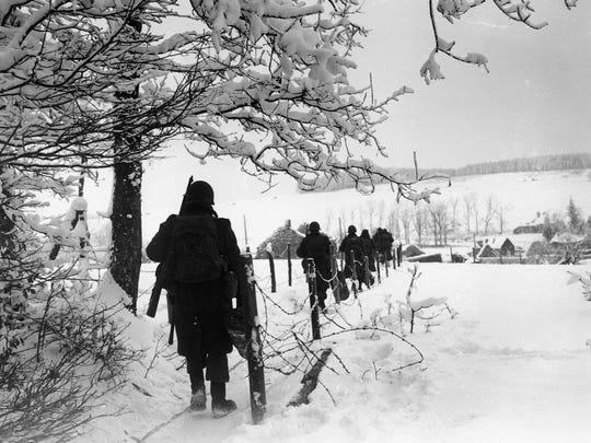 Troops of the 3rd U.S. Army march toward the village