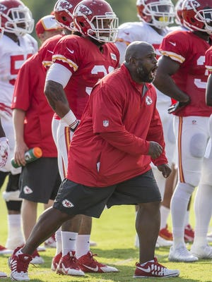 Kansas City Chiefs assistant coach Eric Bieniemy instructs players during 2014 training camp in St. Joseph, Mo. NFL teams must conduct training camps at their own facilities this season.