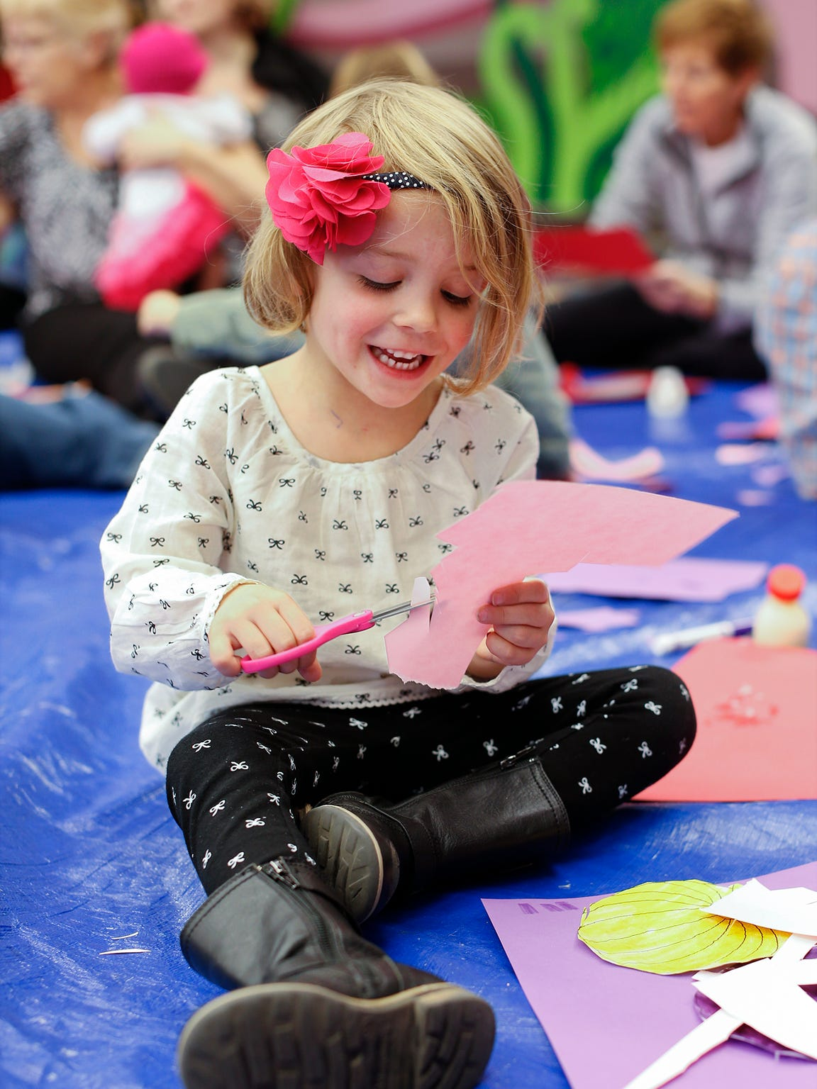 Kamri Neuman, 3, cuts paper into shapes as she works on a craft project in the Kid's Place at the Great Falls Public Library.