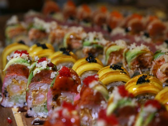 A platter covered in a variety of sushi rolls at Bubble