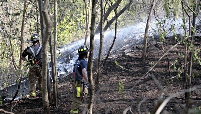 Firefighters battle a brush fire just north of the Hartsdale Metro-North station.