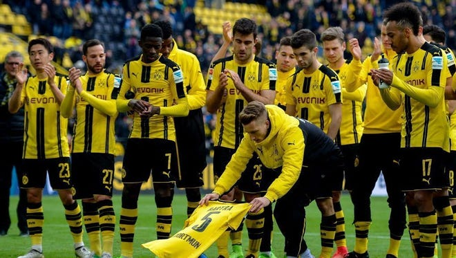 Borussia Dortmund's Marco Reus lays the shirt of Marc Bartra, who was injured during the bus attack on the team.