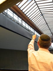 Joel Shandelman, chief energy officer for Bell Works, points out to new solar glass being installed in the Holmdel building.