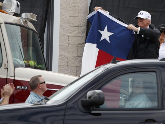 President Donald Trump, accompanied by first lady Melania Trump, holds up a Texas flag after speaking with supporters outside Firehouse 5 Corpus Christi, Texas, Tuesday, Aug. 29, 2017, following a briefing on Harvey relief efforts. (AP Photo/Evan Vucci)