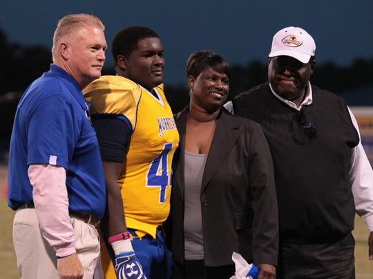 D.J. Jones stands alongside Wren coach Jeff Tate (left) and his parents while being honored before his Senior Night game in 2012.
