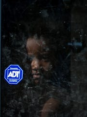 A child stares out the front screen glass door where a man was shot at 10th and Bennett Streets in Wilmington.